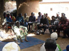 Dr Djimde (seated on chair, far right) meeting with Malian village leaders to obtain permission to collect blood samples from villagers.