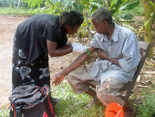 Researcher takes a blood sample from a villager to collect malaria parasites for analysis.