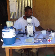 Researcher looking at blood smears in a village field laboratory.